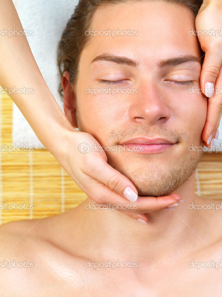 Close up of a man receiving facial massage from a woman, while on holiday at the beauty spa  Stock Photo #3233032