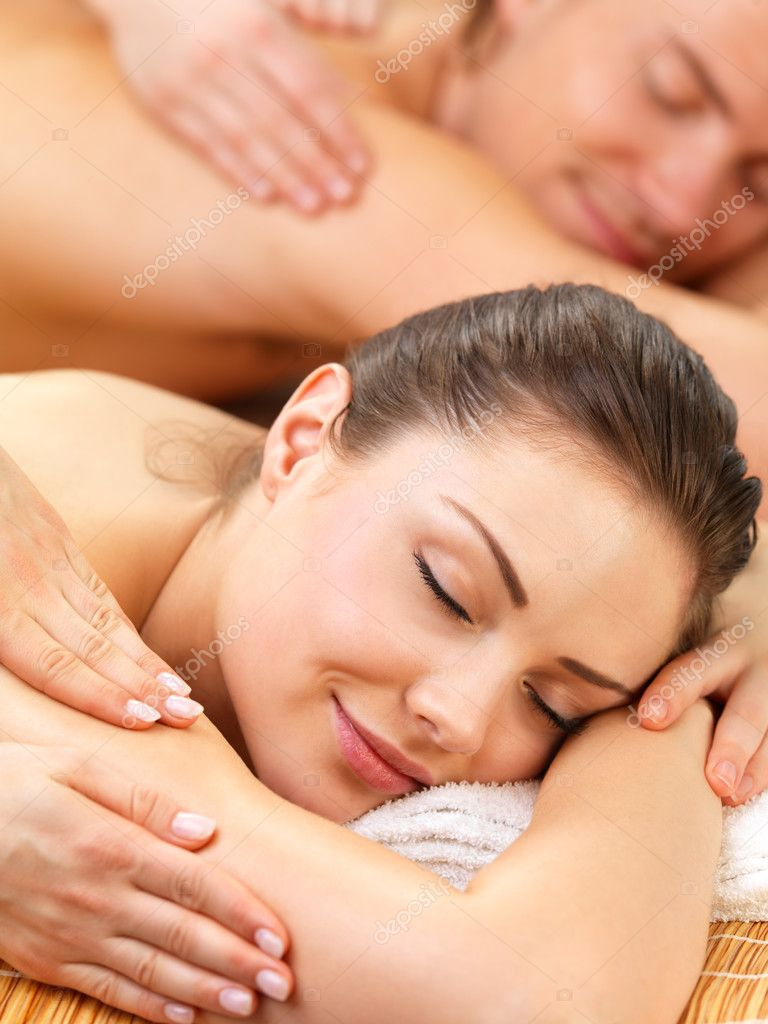 Close up portrait of a romantic couple, on a spa holiday, having a back massage  Stock Photo #3233311