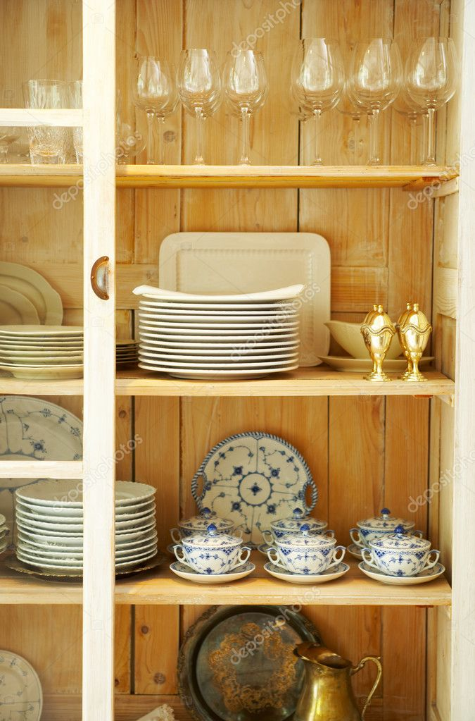 A close-up picture of a beautiful old cupboard, filled with plates, glasses and dishes.  Stock Photo #3236226