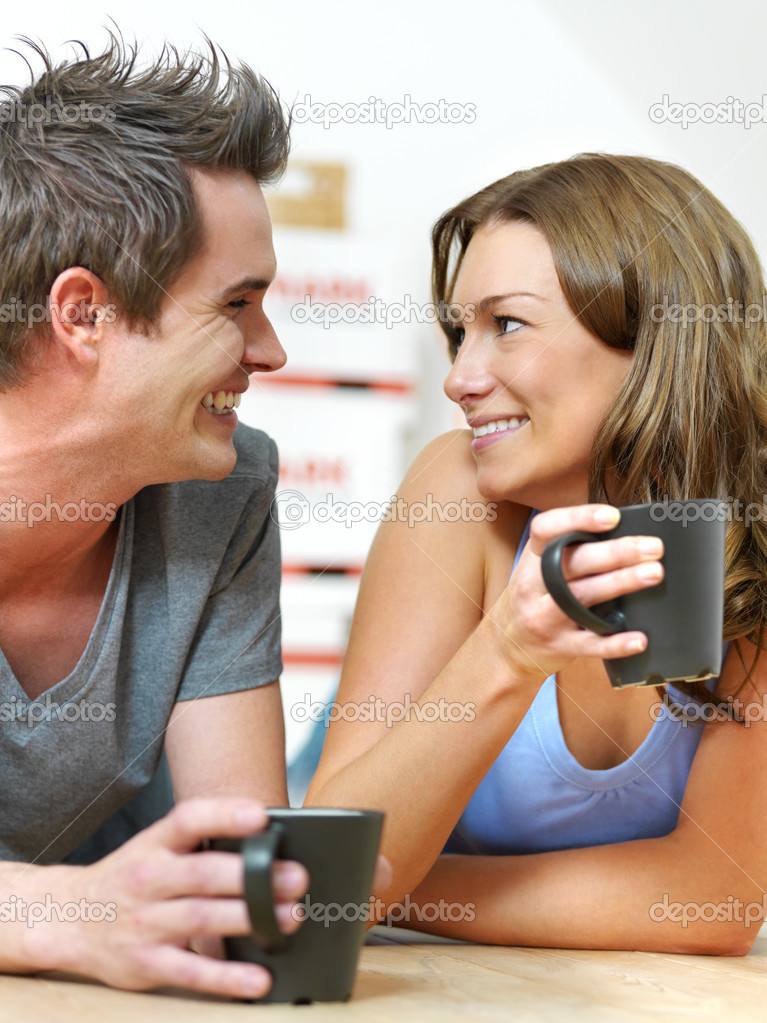 Attractive couple lying on the floor at home with coffee cups and smiling at each other  Stock Photo #3236855