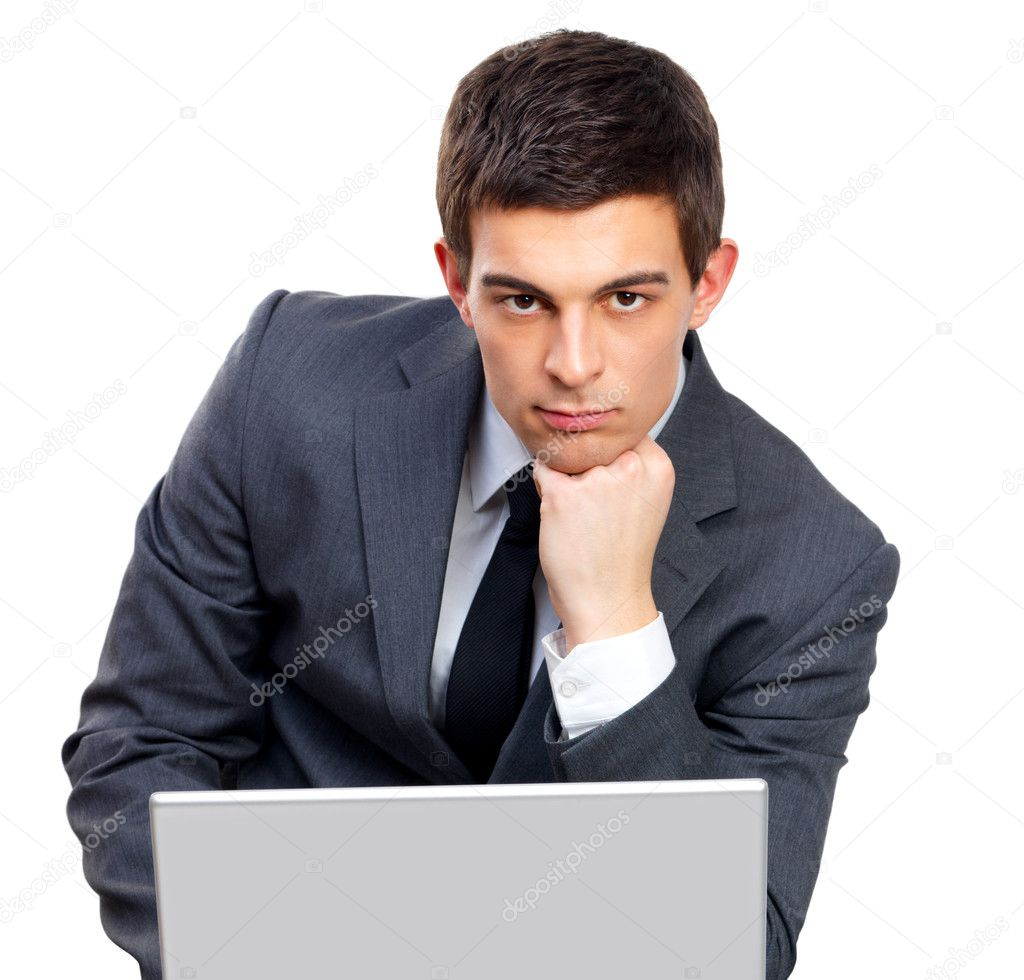 Portrait of a young businessman sitting by his laptop working, looking serious and tired. — Stock Photo #3237505