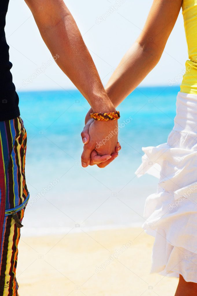 The worlds two best things: Sunshine and Romance. A young couple holding hands on the beach in Greece — Stock Photo #3238268