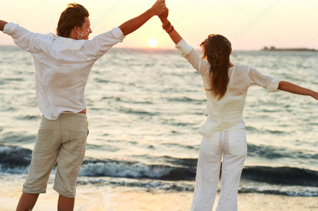 A young couple standing hand in hand with their arms raised on the beach — Stock Photo #3239106