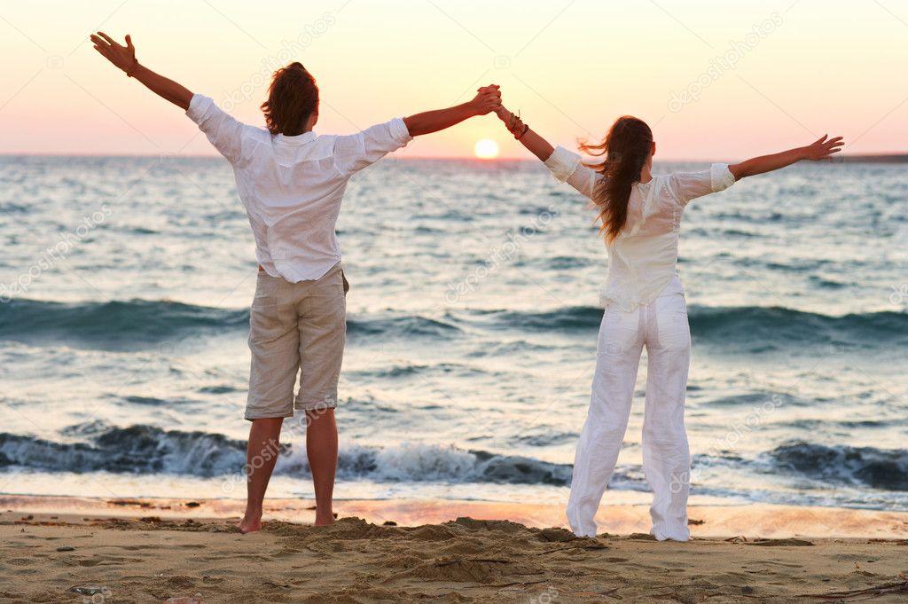 A young couple standing hand in hand with their arms raised on the beach — 图库照片 #3239108