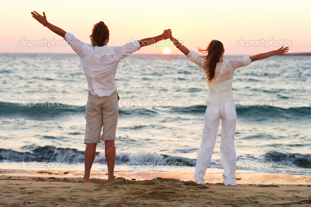 A young couple standing hand in hand with their arms raised on the beach  Stockfoto #3239108
