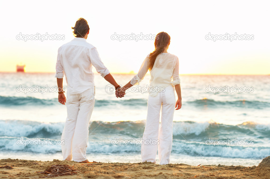A young couple standing hand in hand on the beach  Stock Photo #3239158