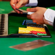 Dealer handling cards at a casino - Stock Photo