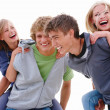 Young men giving women piggyback - Stock Photo