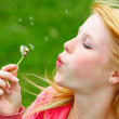 Young teenager blowing a dandelion - 