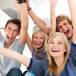 Royalty-Free Stock Photo: Young friends with arms raised in success