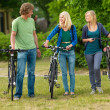 Royalty-Free Stock Photo: Young guys and girls with bicycle in the nature field