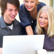 Royalty-Free Stock Photo: Happy young friends using laptop