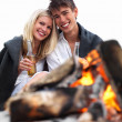 Romantic young couple sitting by bonfire at beach drinking beer - Stock Photo