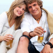 Royalty-Free Stock Photo: Young couple sitting together with beer bottles