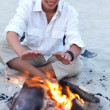 Young guy enjoying bonfire at beach - Stock Photo