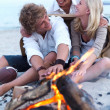 Happy young guys and girls enjoying bonfire at beach in summer - Stock Photo