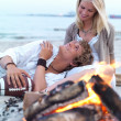 Young couple sitting by bonfire at beach in summer - Stock Photo