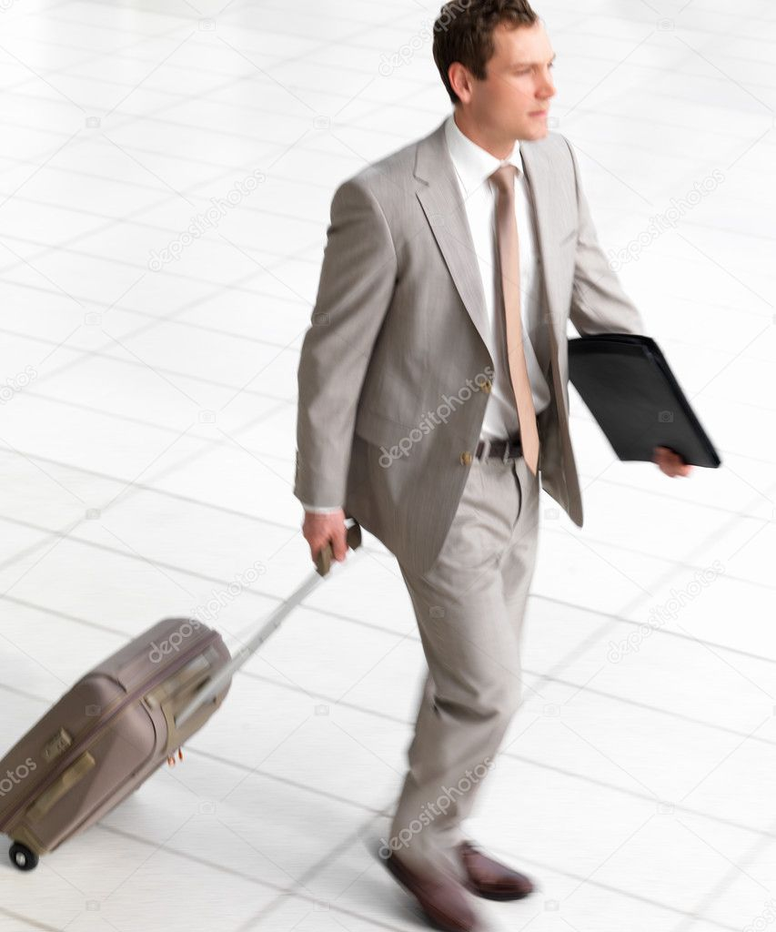 Portrait of a young successful smiling business man walking with travel bag  Stock Photo #3242744