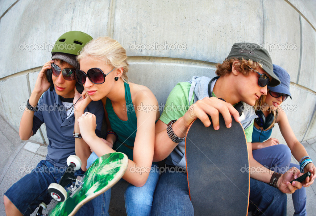 View of young couples sitting side by side, listening music. Street smart kids — Stock Photo #3243428