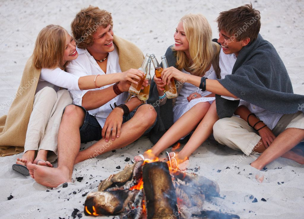 Happy young friends toasting beer bottles at beach by the fire — Stock Photo #3243831