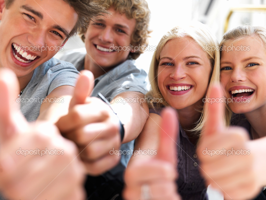 Happy guys and girls expressing happiness by showing thumbs while smiling — Stock Photo #3246539