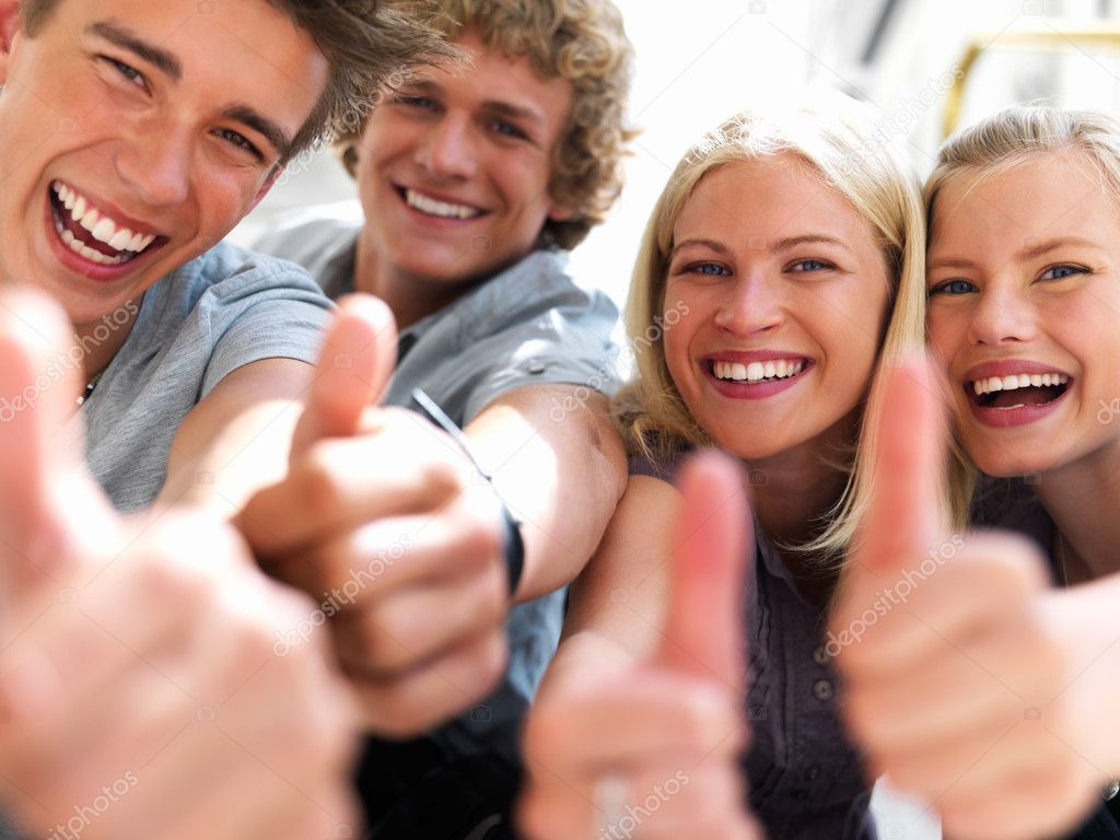 Happy guys and girls expressing happiness by showing thumbs while smiling  Photo #3246539