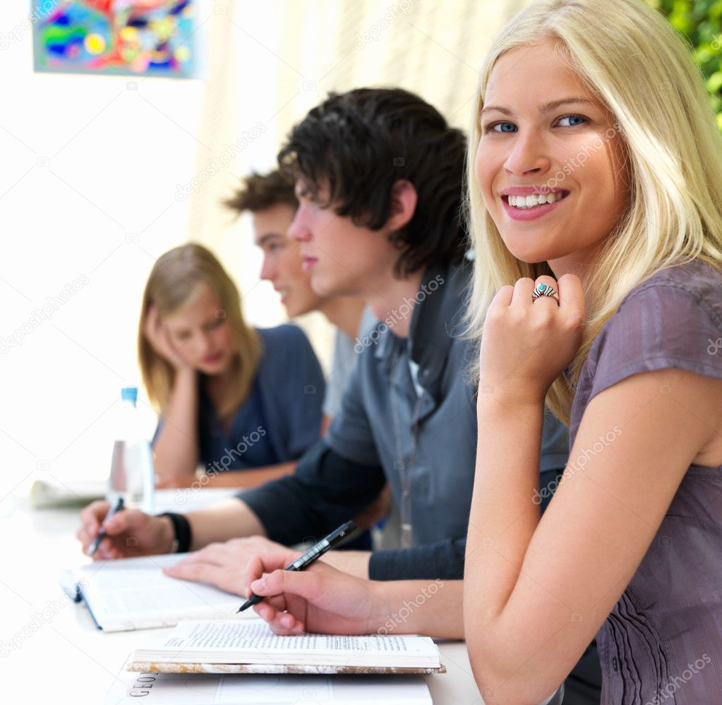 Portrait of happy young girl sitting with her friends in school — Stock Photo #3246599