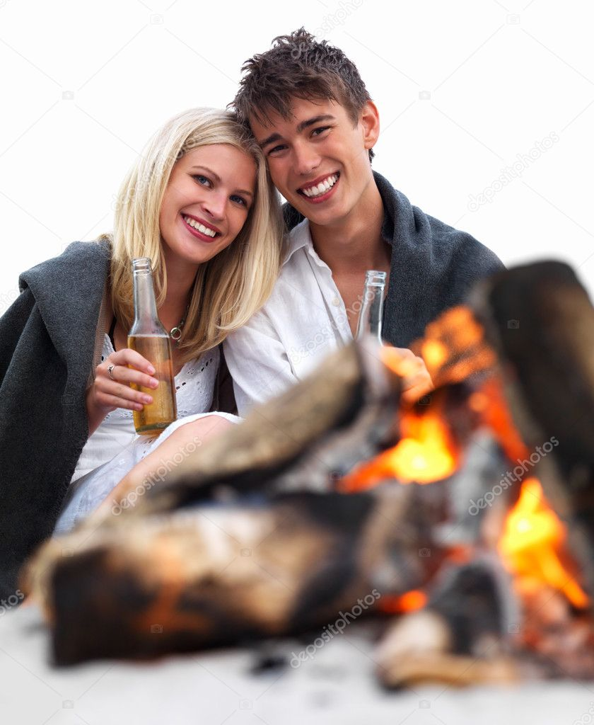 Portrait of a romantic young couple sitting by bonfire at beach drinking beer  Stock Photo #3246919