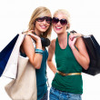 Happy young girls standing with shopping bags - Stock Photo