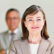Portrait of a smiling businesswoman with colleague - Stock Photo
