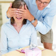 Royalty-Free Stock Photo: Happy old man closing eyes of his wife with gifts in front