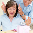 Royalty-Free Stock Photo: Happy old man surprising his wife with gifts