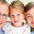 Royalty-Free Stock Photo: Happy grandparents looking at camera with their granddaughter