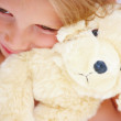 Portrait of a cute girl hugging her teddybear - Stock Photo