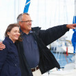 Happy old couple standing together at harbor - Stock Photo
