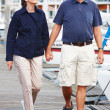 Royalty-Free Stock Photo: Old couple walking together on jetty by harbor