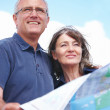 Royalty-Free Stock Photo: Happy old couple looking ahead with map in hand