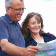 Happy old couple holding map - Stock Photo