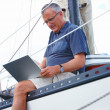 Royalty-Free Stock Photo: Old man using laptop while sitting at the edge of a ship