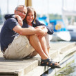Royalty-Free Stock Photo: Happy old couple sitting on quay by sea