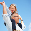 Grandfather holding his granddaughter on his shoulders - Stock Photo