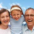 Portrait of grandparents with granddaughter having fun - Stock Photo