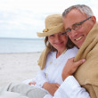Royalty-Free Stock Photo: Portrait of romantic old couple sitting together at beach