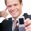 Happy young businessman holding mobile phone and gesturing - Stock Photo