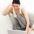 Royalty-Free Stock Photo: Happy young woman sitting on sofa using laptop