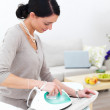 Royalty-Free Stock Photo: Happy young lady ironing her clothes