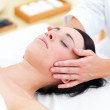 Beautiful young lady receiving facial massage at day spa - Foto Stock