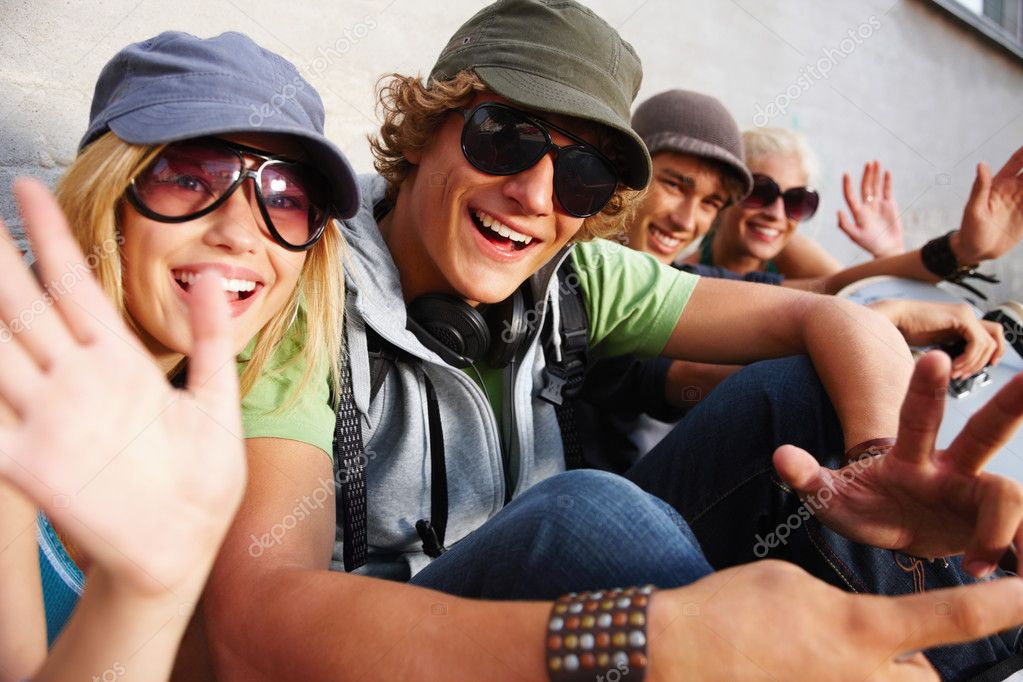 Group of young guys and girls sitting together and having fun — Stock Photo #3268049