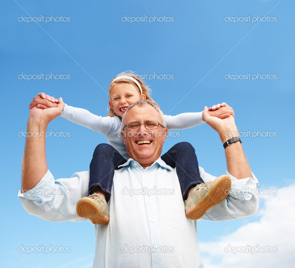 Closeup portrait of happy grandfather holding his granddaughter on his shoulders against sky — Stock Photo #3268576