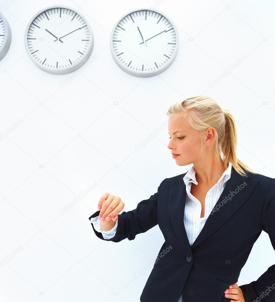 Portrait of a business woman checking time in front of a wall with clocks — Stock Photo #3269465